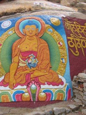Boeddha geschilderd op een rotswand in Tibet.